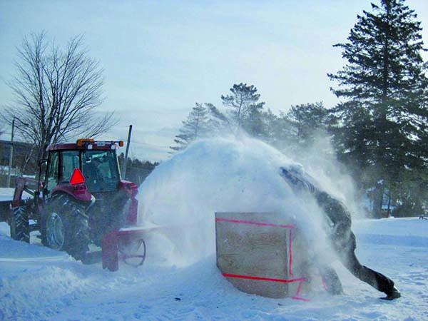 Fabrication d'un bloc. Michel Côté sous la neige, Dominique Daigle au tracteur. Photo par Dominique Langevin