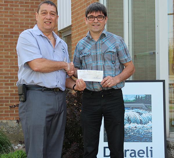 Le maire de la Ville de Disraeli, M. Jacques Lessard, remettant le chèque au montant de 1 000$ au responsable de l'Harmonie M. Mario Daigle.
