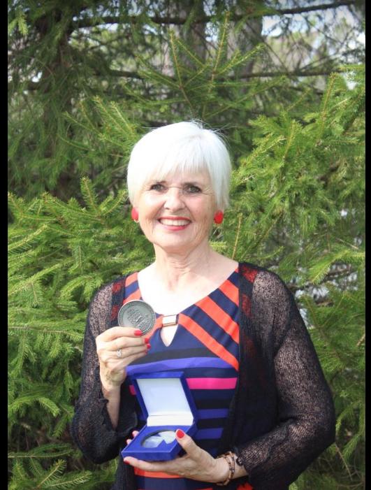 Fernande Raymond tenant fièrement sa médaille du Lieutenant-gouverneur